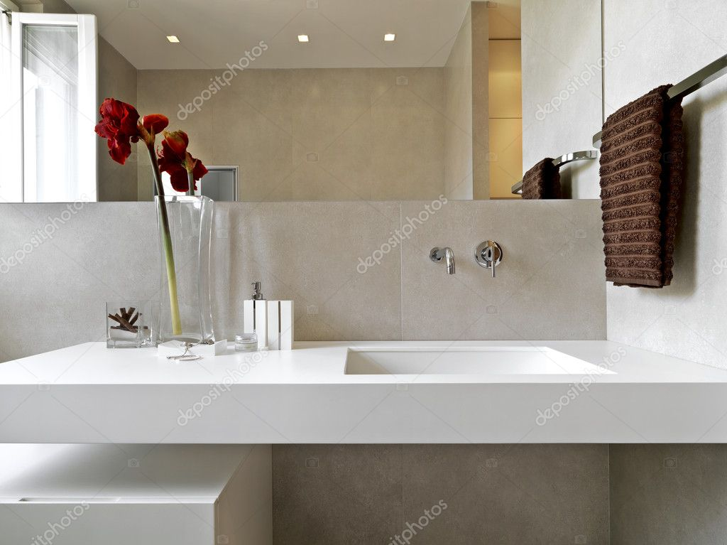 Detail of washbasin in a modern bathroom with brown towel and vase of red flowers — Stock Photo #7446185
