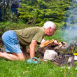 Senior man trying to make a bonfire — Stock Photo #7222368