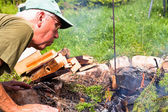 Senior man making bonfire — Stock Photo