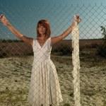 Young woman wating behind metallic fence — Stock Photo #6835297