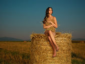 Young woman watching sunset on hay stack — Stock Photo