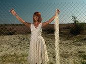 Young woman wating behind metallic fence — Stock Photo