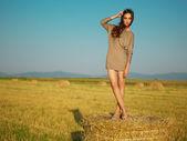 Krásná žena, která stála na západ slunce seno zásobníku — Stock fotografie