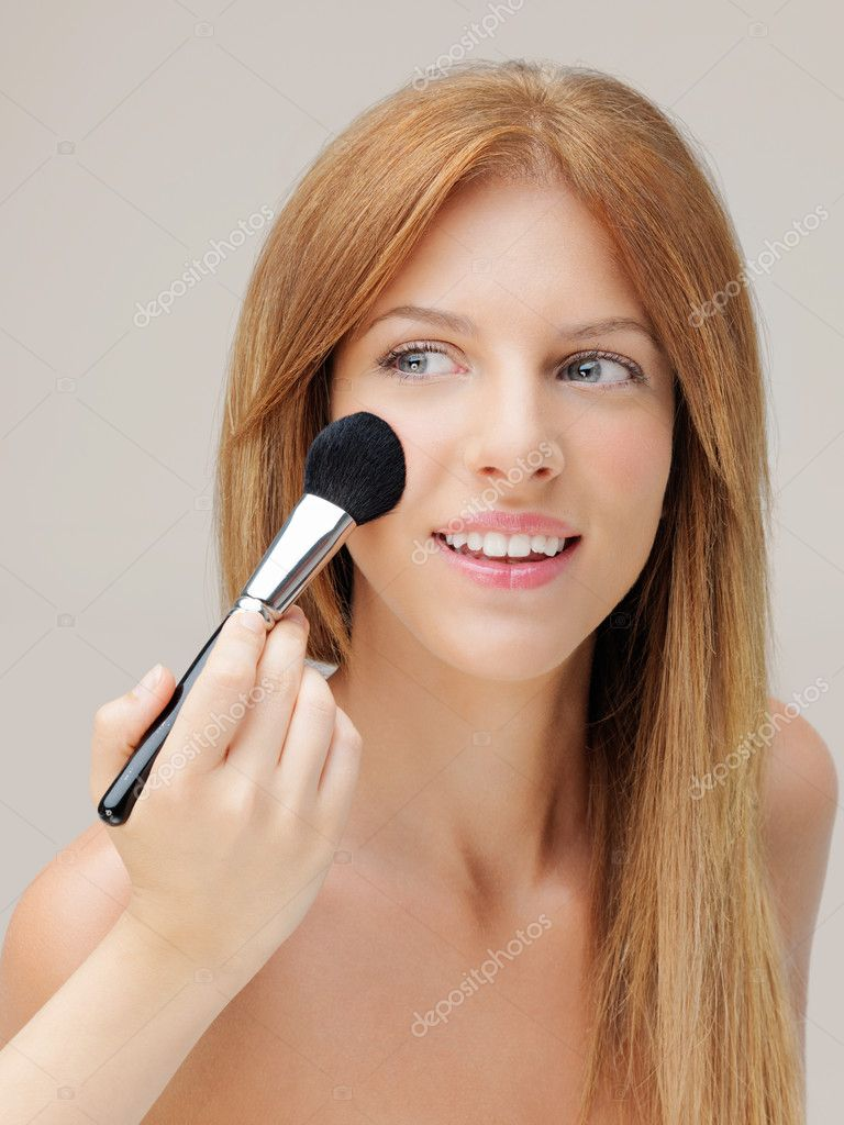 Happy young woman applying blusher on cheeks — Foto Stock #6835772