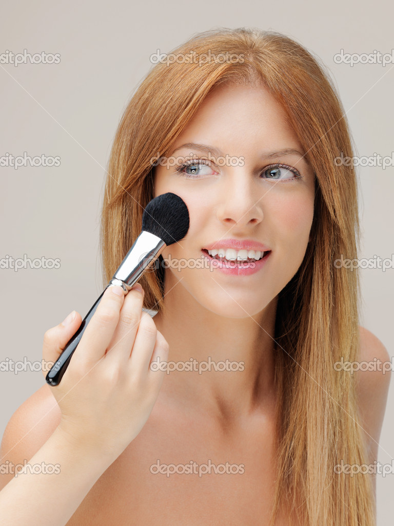 Happy young woman applying blusher on cheeks — Stok fotoğraf #6835772
