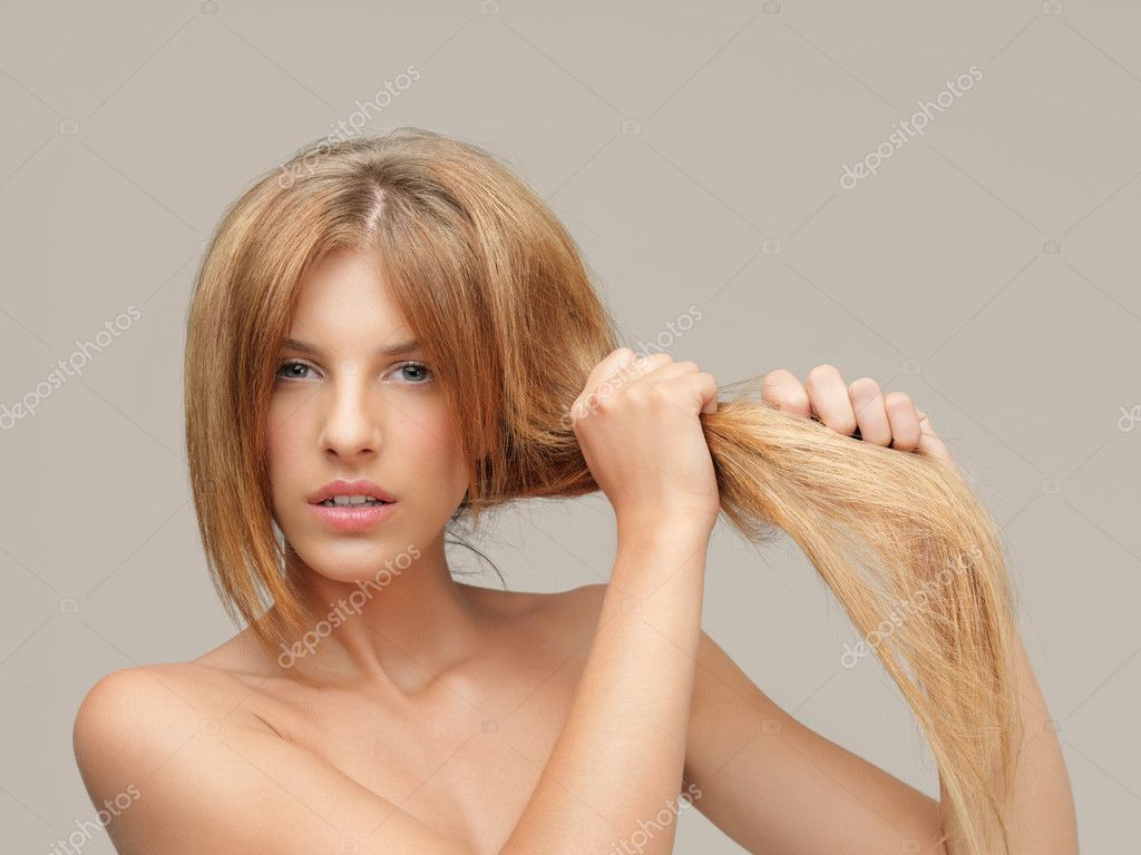 Young woman pulling damaged hair both hands — Stock Photo #6836251
