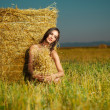 Beautiful nude woman sitting near hay stack — Stock Photo