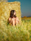 Beautiful nude woman sitting near hay stack — Stock Photo