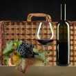Red wine bottle, glass, grapes, picnic basket - Stockfoto