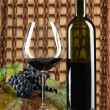 Red wine bottle, glass, grapes, wicker background - Stock Photo