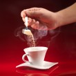 Hand pouring sugar in coffee cup — Stock Photo