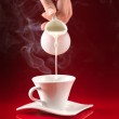 Hand pouring milk in coffee cup — Stock Photo