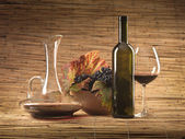 Red wine bottle, glass, grapes, decanter rustic — Stock Photo