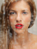 Beauty portrait of woman behind wet window — Stock Photo