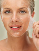 Young woman peeling off a facial mask — Stock Photo