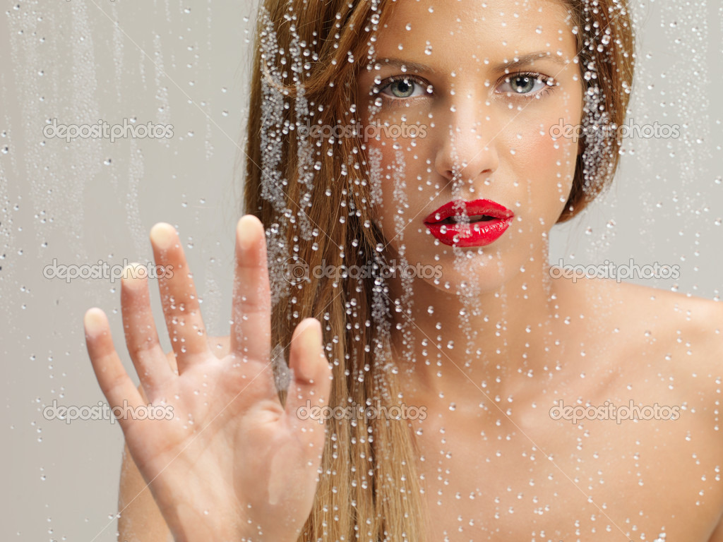 Closeup beauty portrait of blonde woman waving at the camera from behind a wet window — Photo #7279404