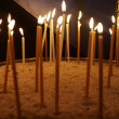 Candles in the sand in church, Greece - Stock Photo