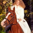 Smiling young bride sitting  on  horse in forest — Foto de Stock