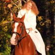 Smiling young bride sitting on horse in forest — Stock Photo