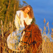 Stock Photo: Beautiful bride siting on red horse at sunset