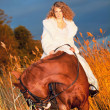 Beautiful bride siting on red  horse at nigth - Stock Photo