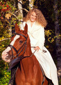 Smiling young bride sitting on horse in forest — Stok fotoğraf