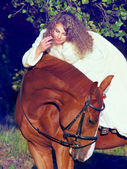 Soft portrait of beautiful young bride with sorrel horse — Stock Photo