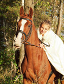 Young bride ride on sorrel horse in forest — Stock Photo
