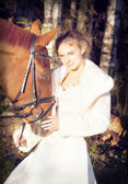 Portrait of bride with horse at forest background — Stock Photo