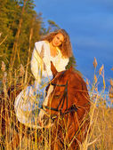Beautiful bride siting on red horse at sunset — Stock Photo