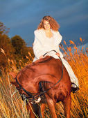 Beautiful bride siting on red horse at nigth — Stock Photo