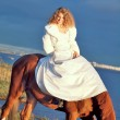 Bride ride on red  horse in gulf at evening — Stock Photo