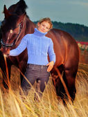 Women with her horse at fall evening in the field — Stock Photo