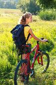 Frau Radfahrer mit Fahrrad und Rucksack — Stockfoto