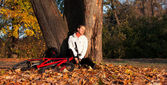 Woman cyclist sits leaning against a tree and enjoy recreation — Stock Photo