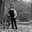 Womcyclist with bike and backpack in autumn park on morning — Stock Photo #7412923