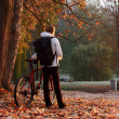 Woman cyclist with bike and backpack in autumn park on the morni - Foto de Stock