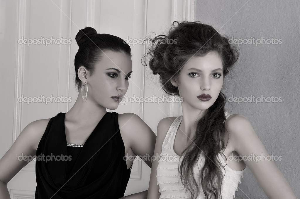 Two beautiful girls with amazing styles and elegant dresses posing indoor near an old fashion door posing with attractive poses and attitude towards the camera  Stock Photo #6801085