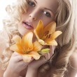 Blond curly woman holding lily — Stock Photo #6840650