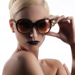 Fashion shot of blond girl with golden sunglasses — Stock Photo #6856888