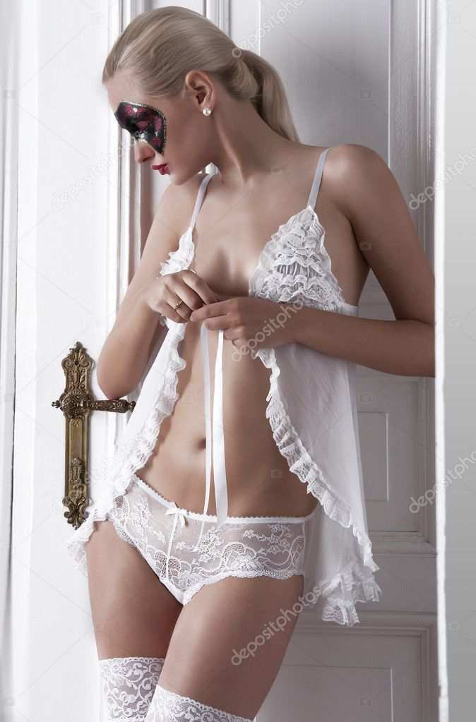 Sexy blonde posing in white lingerie and a painted face ...
