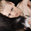 Sexy blonde laying on black just wearing fur — Stock Photo