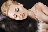 Sleeping blonde beauty on fur — Stock Photo