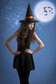Söta halloween häxa poserar under stjärnorna — Stockfoto