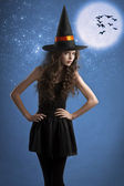Sweet halloween witch posing under the stars — Stok fotoğraf