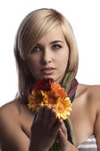 Pretty blonde holding orange red flowers — Stock Photo
