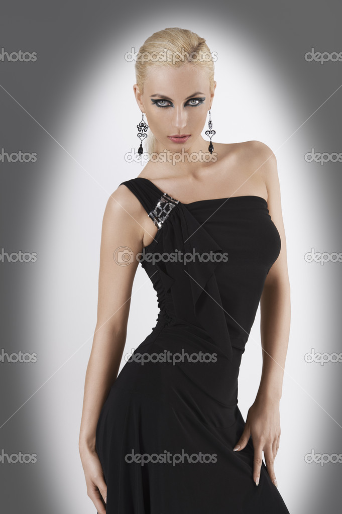 Blond attractive young woaman in black dress and black earring looking in camera with strong and sexy eyes and wit sexy pose looking towards the camera — Stock Photo #7224640
