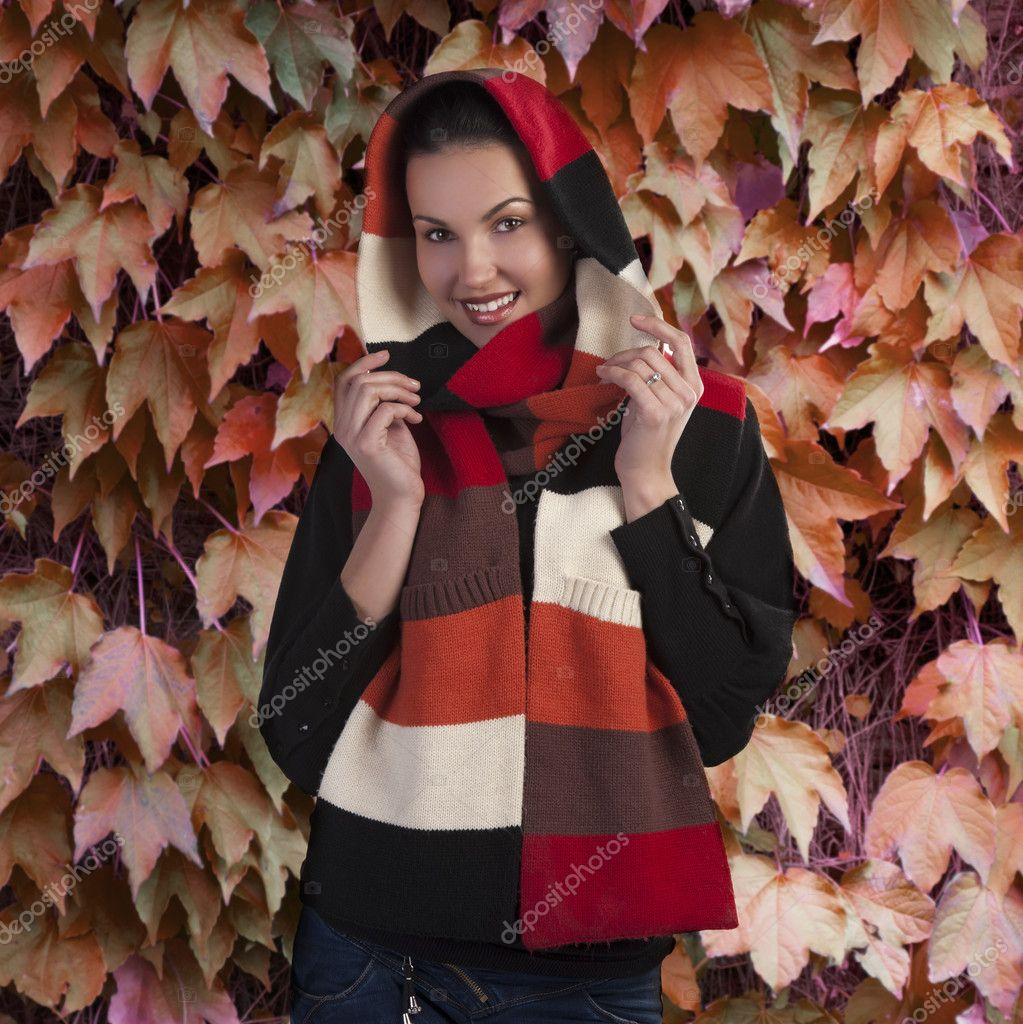 Autumn shot of a young beautiful brunette wearing a dark sweater and a fall color long scarf  — Stock Photo #7267355