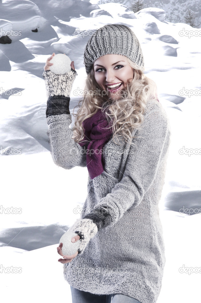 Pretty young girl with curly blond hair in winter dress with hat and scarf playing and laughing to the camera — Stock Photo #7304081