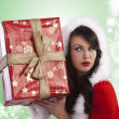 Santa claus lady wondering whats in gift box - Stockfoto
